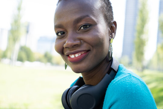 black african woman looking directly at kla camrea with a wireless headset on her neck with a smile on her face, close up