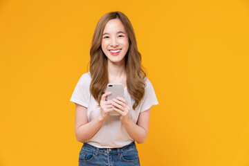 Fototapeta Beautiful Asian woman holding smartphone and smiling with typing on mobile, light yellow background. obraz