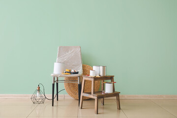 Chair and step ladder with cans of paints near color wall