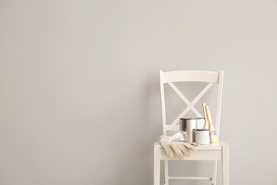 Chair with cans of paints and tools near light wall