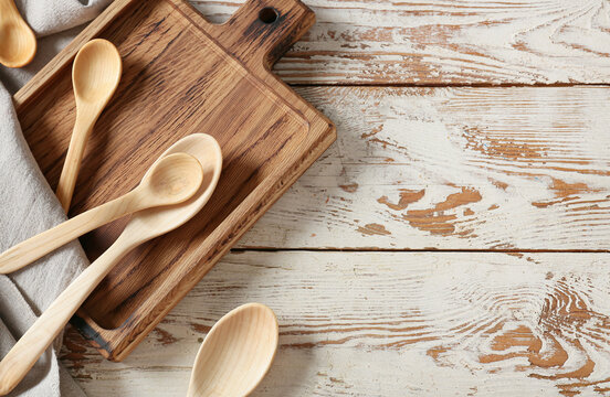 Spoons and chopping board on light wooden background