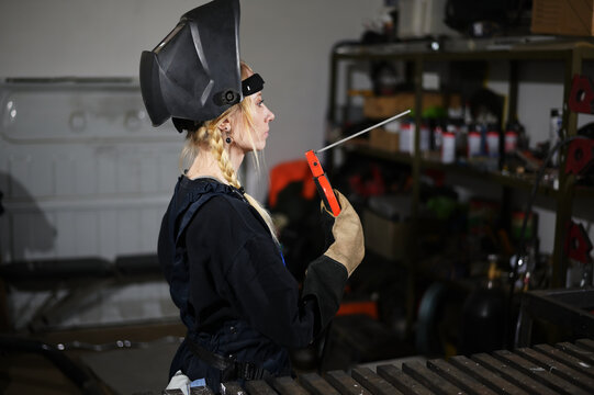 Portrait of cute caucasian blonde girl welder working in a mask in the garage