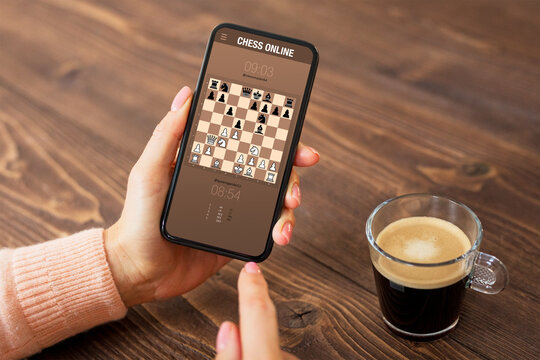 Person playing chess online on mobile phone