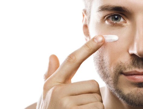 Men's beauty. Young man is applying moisturizing and anti aging cream on his face