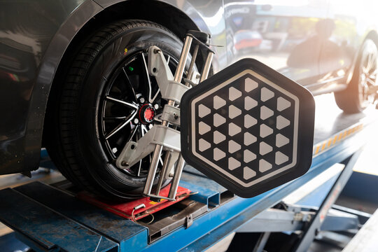 Car wheel balancer calibrate with laser reflector attach on each tire to center driving adjust. Car in auto service. Balancing tire wheel machine.
