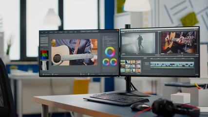 Obraz Video production studio with nobody in it and computer with two displays processing video film montage in new software. Empty movie editing creative start up agency with no people - fototapety do salonu
