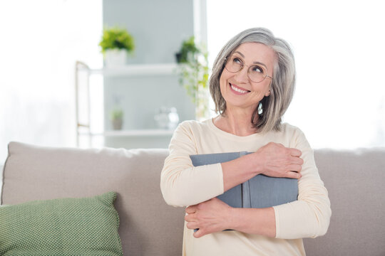 Portrait of positive person sit on sofa arms hugging book look interested far imagine toothy smile free time home indoors