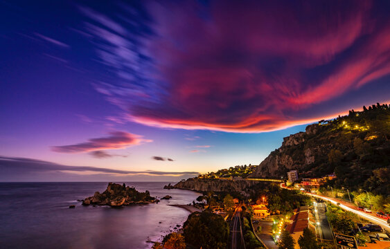 Purple lenticular cloud at sunset over the beach of Isola Bella Nature Reserve in Taormina, Sicily
