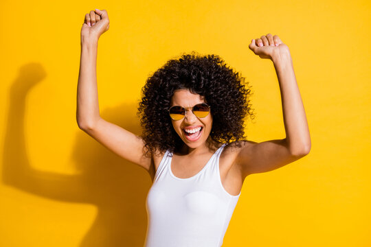 Photo of happy cute dark skin young woman raise fists funky mood isolated on shine yellow color background
