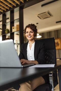 Beautiful businesswoman working on laptop, portrait.