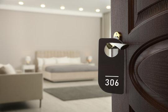 Wooden door open into modern hotel room, closeup