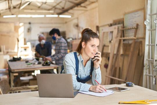 Handwerker Frau bei Kundengespräch am Telefon