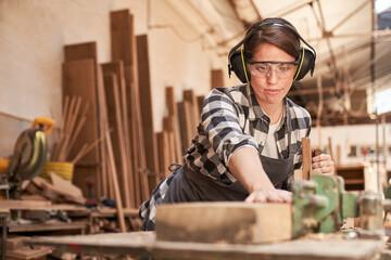 Fototapeta Schreiner Azubi mit Gehörschutz beim Holz hobeln obraz