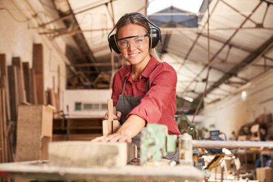 Frau in der Schreiner Lehre arbeitet mit Handhobel