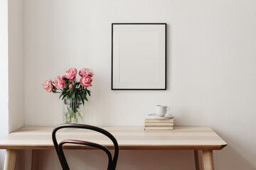 Living room, indoor still life. Empty picture frame mockup on beige wall. Wooden table and old chair. Glass vase with pink peonies bouquet. Elegant working space, home office concept. Interior design.