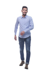 Fototapeta confident young man in jeans striding forward.