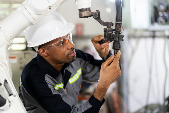African American male engineer worker maintenance automatic robotic arm machine in factory. Black male technician worker checking, repair automatic robot hand machine with screwdriver in smart factory