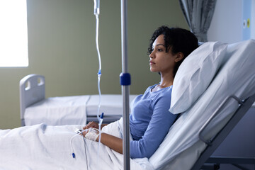 Mixed race female patient sitting in hospital bed wearing fingertip pulse oximeter and iv drip