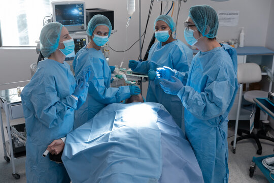Diverse group of male and female surgeons in operating theatre wearing face masks performing surgery