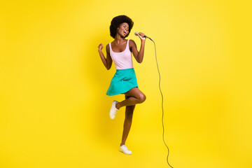Full body photo of dark skin attractive girl wear pink singlet hold sing microphone isolated on yellow color background