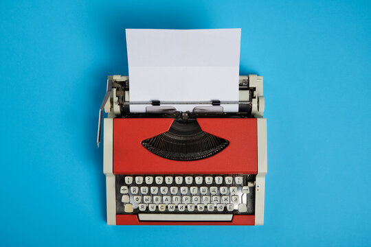 Top view of red vintage typewriter with white blank paper sheet