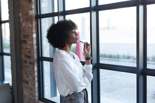 African american woman standing, holding pen and thinking in cafe
