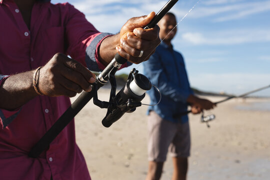 Mid section of african american father and his son with fishing rods fishing together at the beach