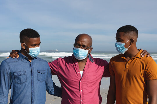 African american father and his two sons wearing face masks standing together at the beach