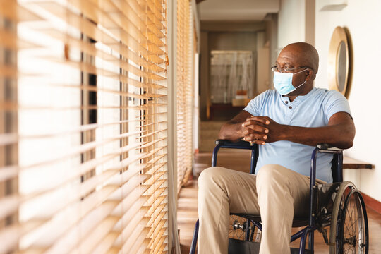 Disabled african american senior man wearing face mask sitting on the wheel chair at home