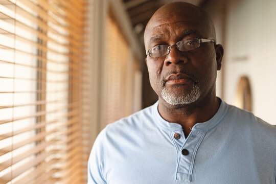Portrait of thoughtful african american senior man standing at home