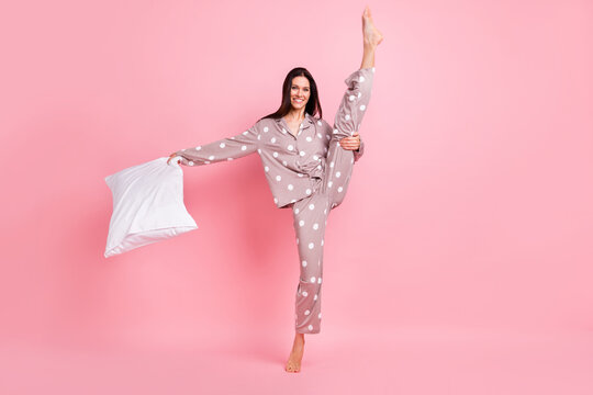 Photo of sweet shiny young lady dotted nightwear holding pillow dancing rising leg isolated pink color background