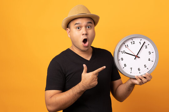 Young asian man wearing hat black shirt holding Big clock standing on isolated yellow background.