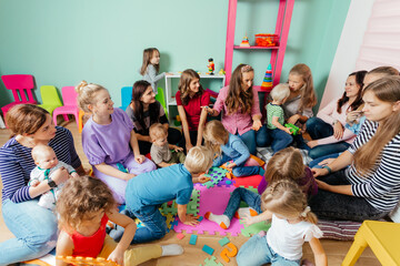 Lovely babies and their mothers at the nursery or daycare