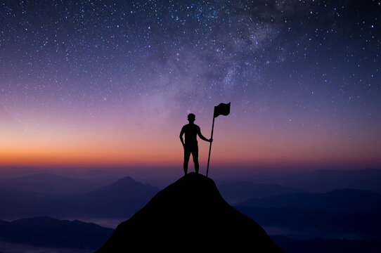 Silhouette of businessman standing on top of the mountain over the sky and star, Milky way with flag. He was delighted and showed the achievement of his goals in his work.