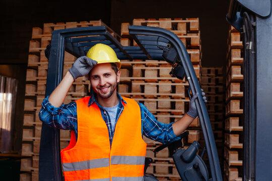 Smiling man posing near industrial stacker forklift at warehouse