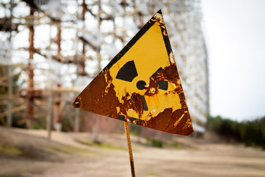 Old yellow radiation sign against the Duga Radar antenna complex. Chernobyl Exclusion Zone, Ukraine. Tilt-shift effect