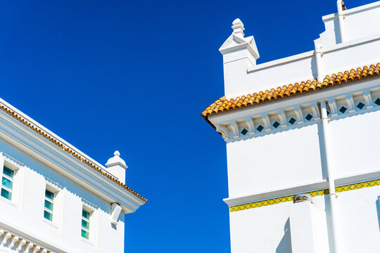 Beautiful white buildings with golden roof tiles on a clear blue sky