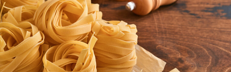 Homemade tagliatelle pasta in brown paper on an old wooden background. Banner.
