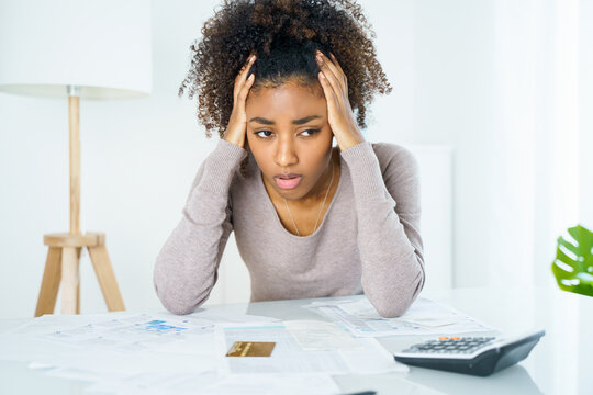 Frustrated young woman reading credit card statement