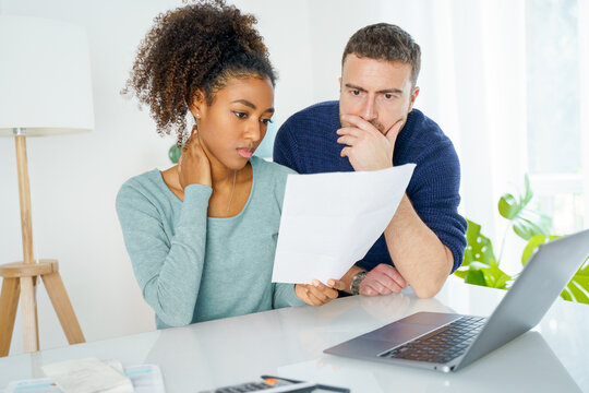 Multiethnic couple worried about family budget and monthly expenses