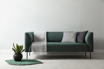 Obraz Stylish living room interior with comfortable green sofa and beautiful plant - fototapety do salonu