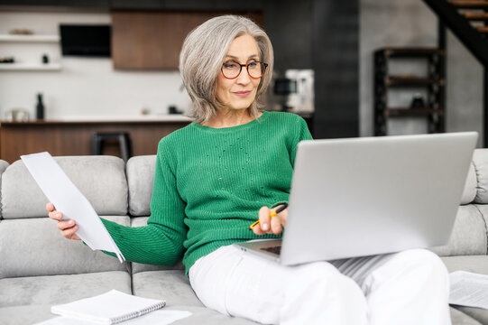 Confident retired woman is calculating house bills, checking spending per month, monitoring savings, senior female sits on the couch at home with a laptop and looking through workpapers, utility bills