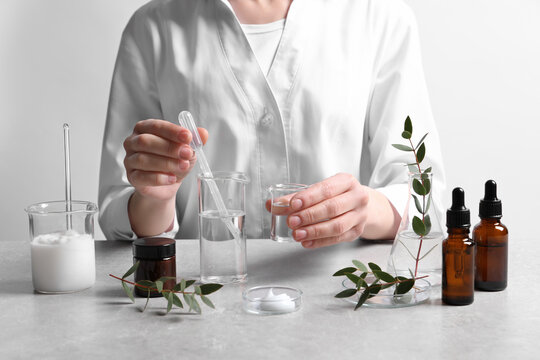 Scientist making cosmetic product at grey table in laboratory, closeup