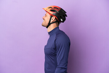 Fototapeta Young Brazilian cyclist man isolated on purple background laughing in lateral position obraz