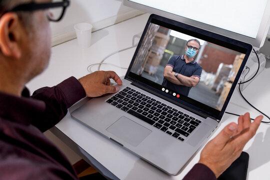 Dettaglio di un computer portatile nel cui schermo compare un uomo con la mascherina  in un magazzino  da remoto in videoconferenza con un altro uomo seduto davanti al computer