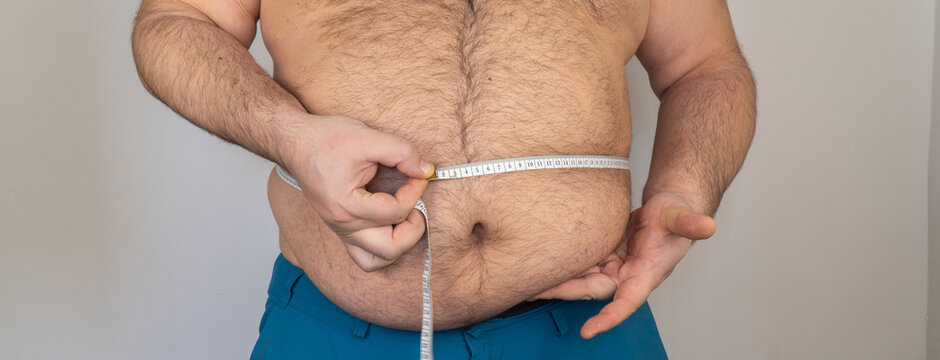 fat man measures the size of the abdomen with a centimeter measuring tape. person is overweight, he is obese. starting a diet