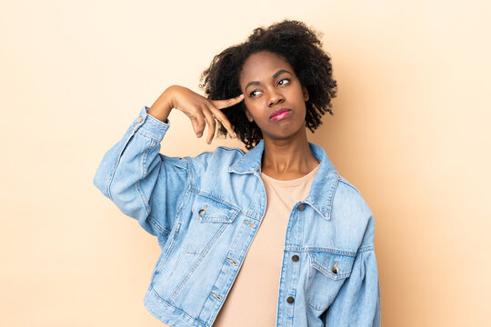 Young African American woman isolated on beige background making the gesture of madness putting finger on the head