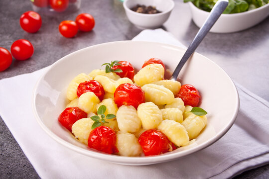 Homemade Italian gnocchi with tomato cherry on the wooden table