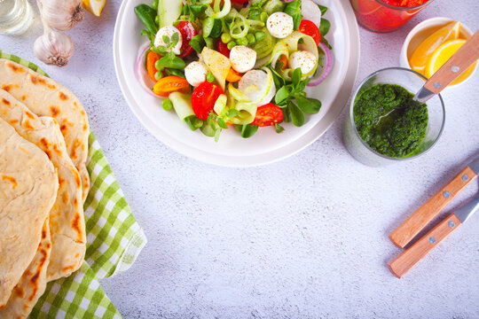 salad of fresh cherry tomatoes, mozzarella, basil and other greens on the dinner table with pita flat bread