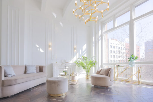 very light and bright interior of luxurious cozy living room with chic soft beige furniture with gold metallic elements, huge window to the floor and wooden parquet